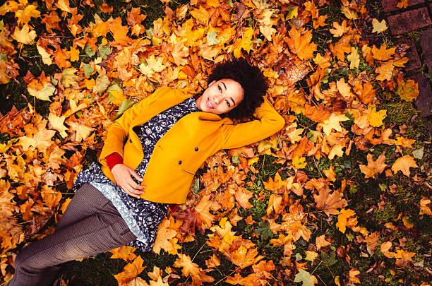 junge frau liegen auf gelbe blätter - laub winter stock-fotos und bilder