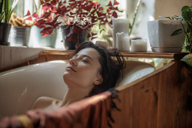 Young woman lying in a bath at home stock photo