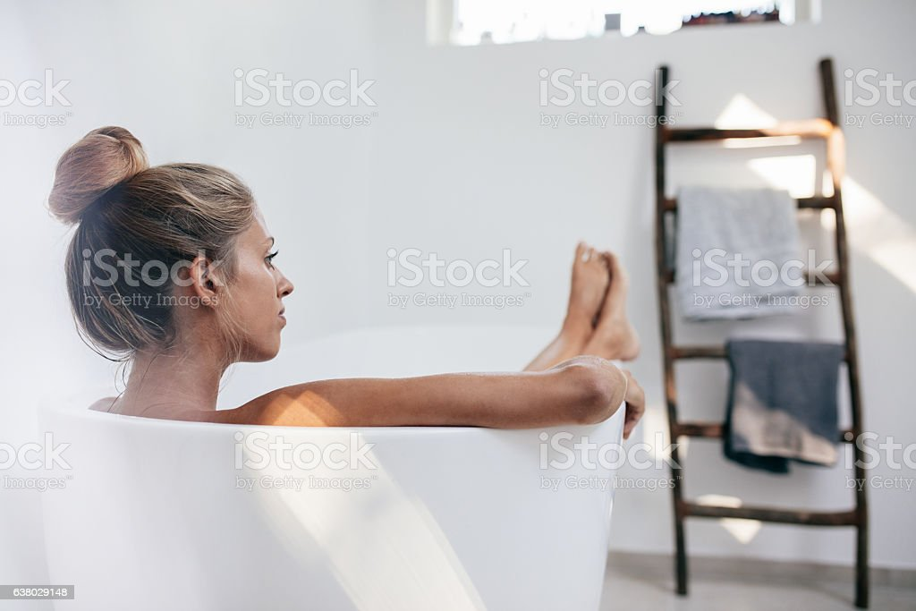 Young woman lying in bathtub and looking away - foto stock
