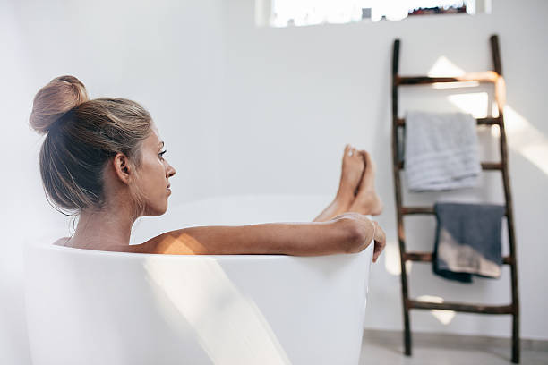 Young woman lying in bathtub and looking away stock photo