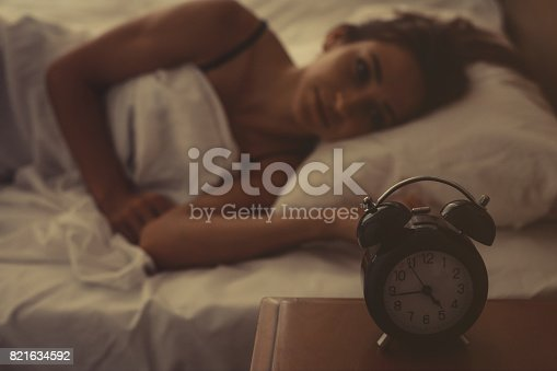 istock Young woman lying in bed 821634592