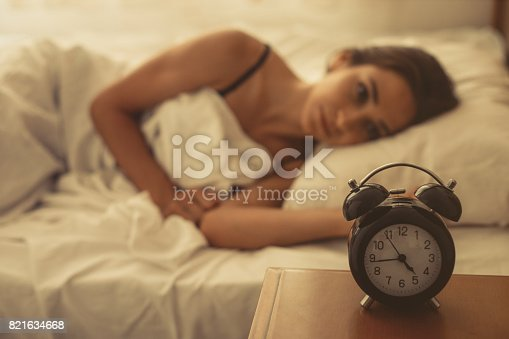 istock Young woman lying in bed 821634668
