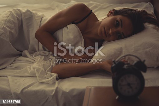 istock Young woman lying in bed 821634766