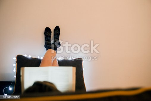 501914364istockphoto Young woman lying in bed while reading a book 641349452