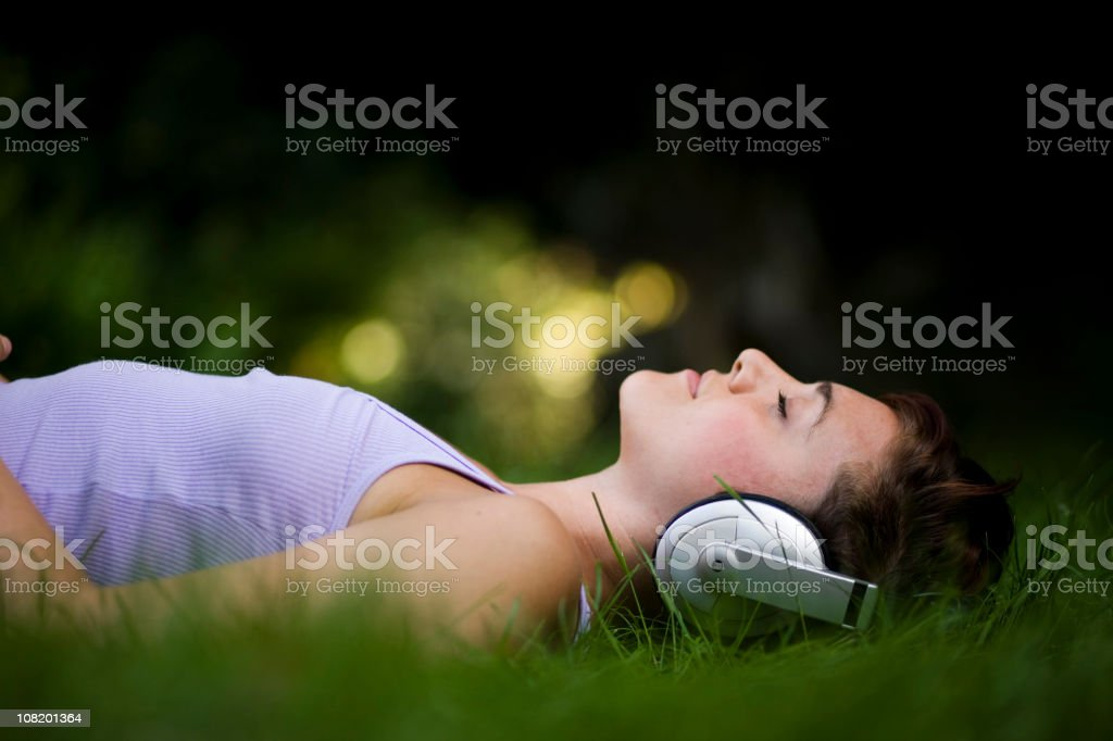 Young Woman Lying in Grass and Listening to Headphones royalty-free stock photo