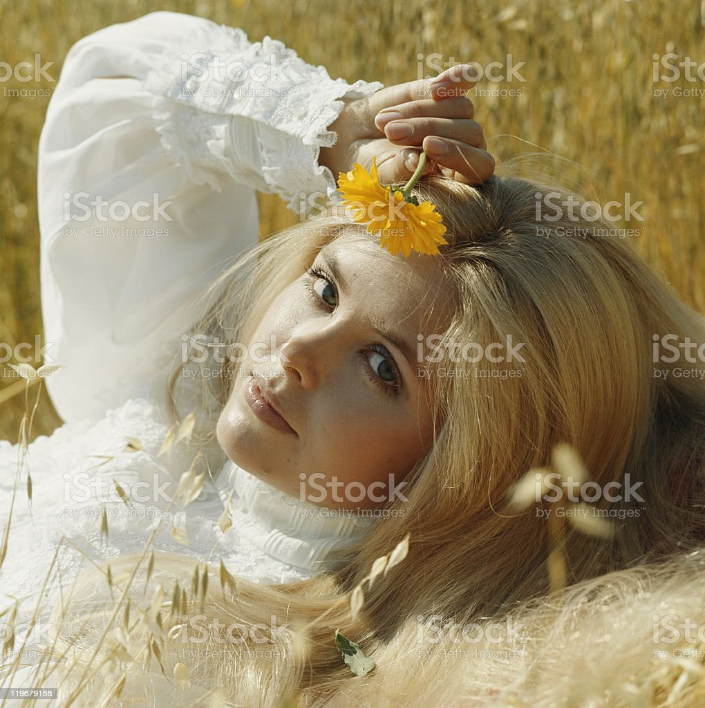Young woman lying in meadow holding flower, portrait stock photo