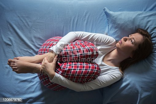 Young woman lying in pain on bed in her pajamas, cold and flu, illness, pms, menstruation, holding hot water bottle