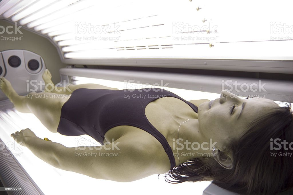 Young Woman Lying in Tanning Bed stock photo