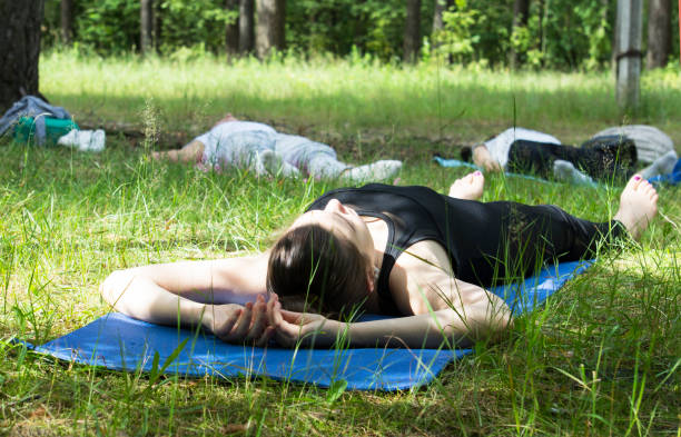 Young woman (yoga coach) lying on a gym mat in relaxed.  Yoga classes in outdoor forest. stock photo