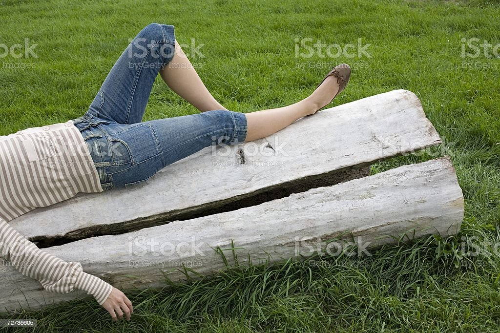 Young woman lying on a log royalty-free stock photo