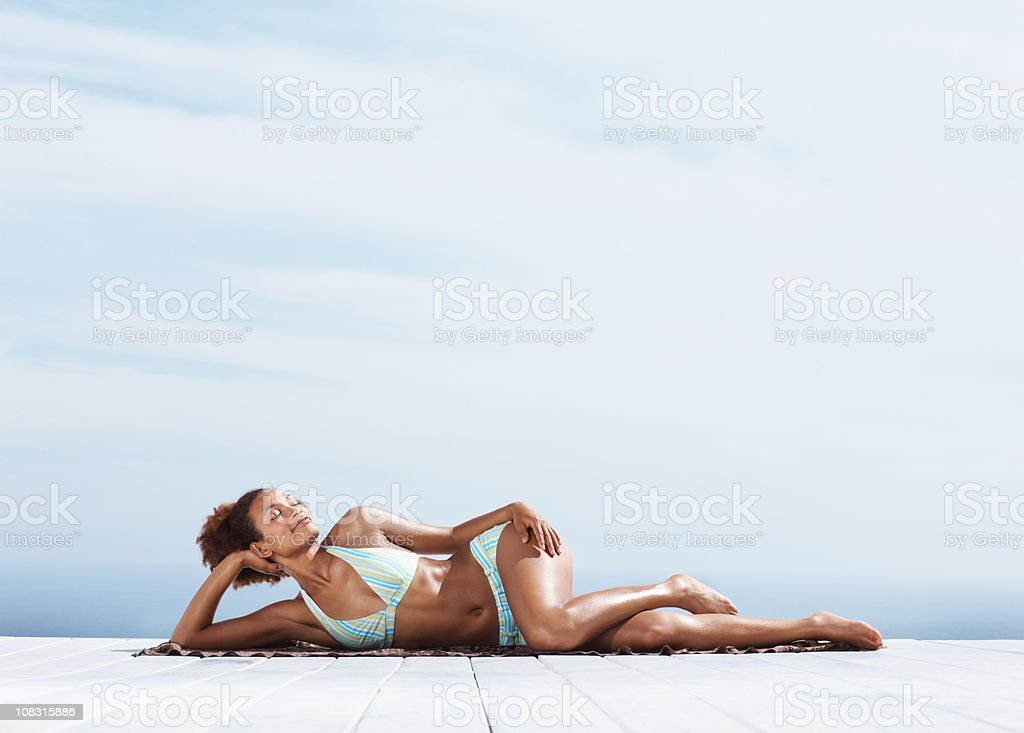 Young woman lying on a porch sunbathing stock photo