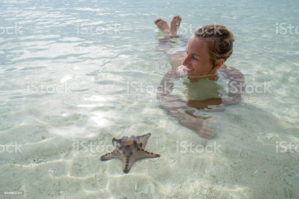 Young woman lying on beach in shallow water, vacations travel exoticism stock photo