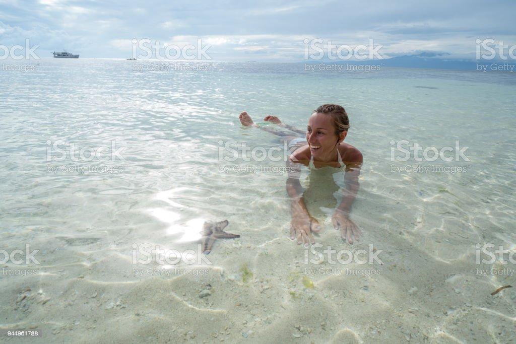 Young woman lying on beach starfish stock photo