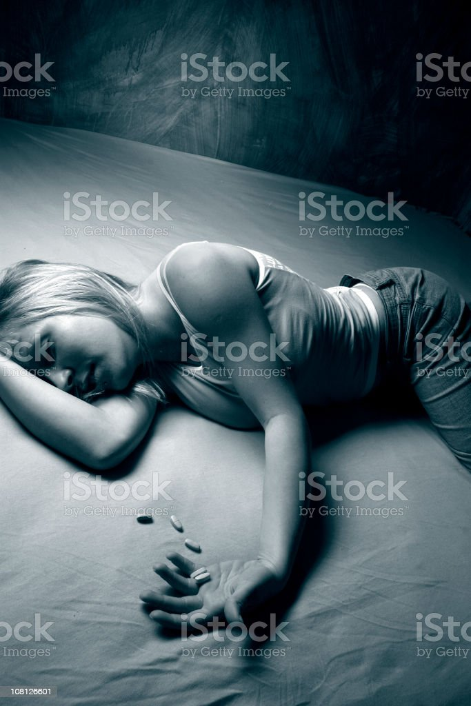 Young Woman Lying on Bed and Holding Handful of Pills royalty-free stock photo