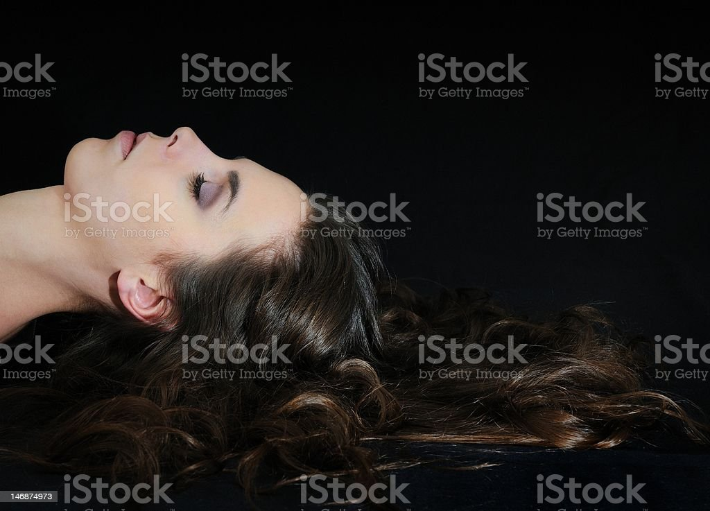 Young woman lying on black with long hair royalty-free stock photo