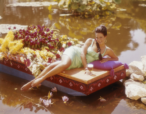 Young woman lying on boat with beer glass beside flowers, smiling, portrait