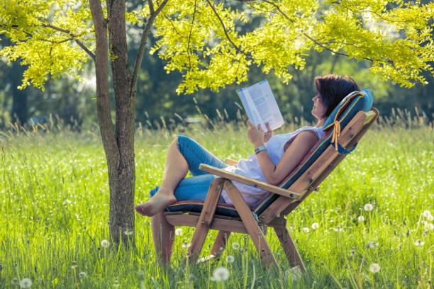 Junge Frau liegt auf Liegestuhl im Schatten unter Baum Buch – Foto