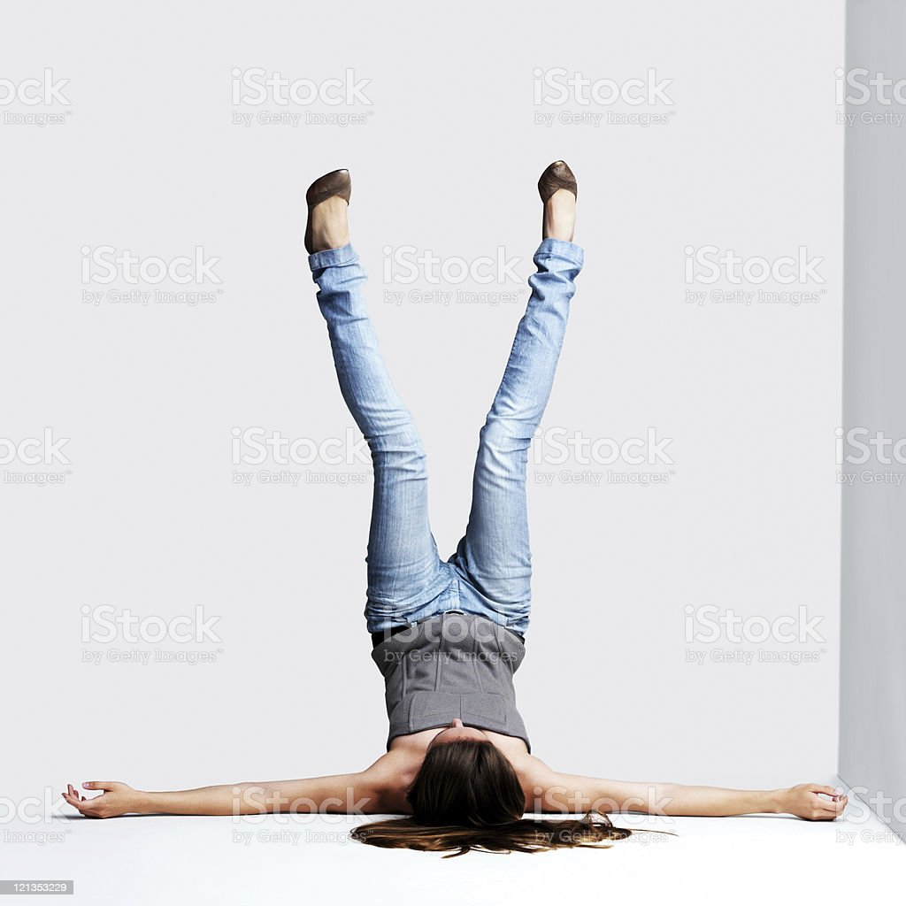 Young woman lying on floor with legs up stock photo
