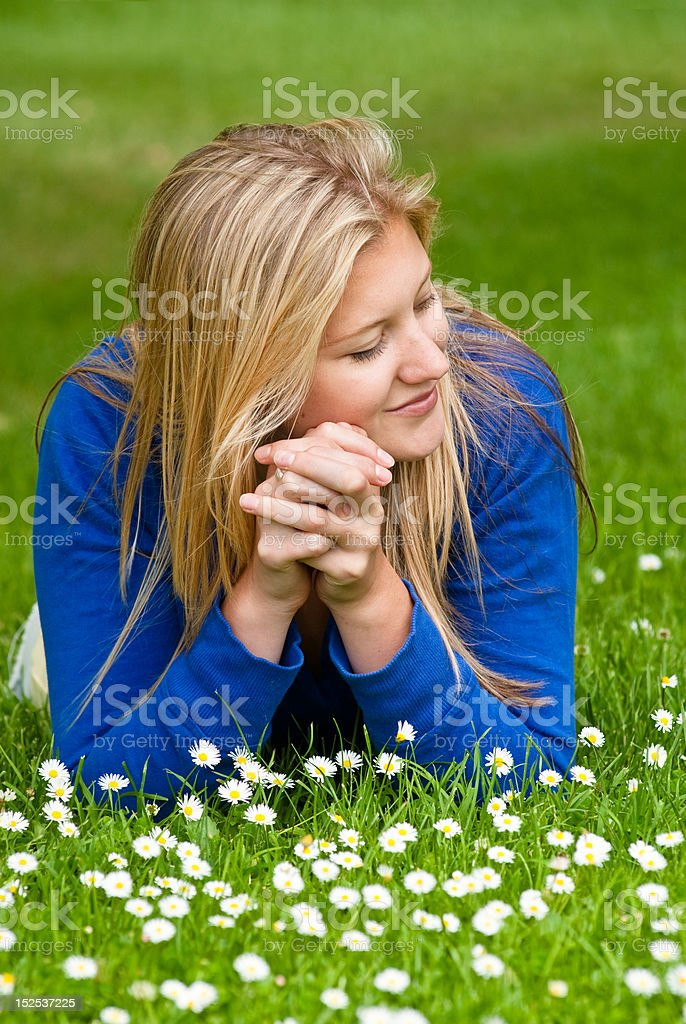 Young woman lying on grass among daisies royalty-free stock photo