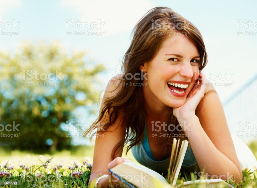 Young woman lying on grass and laughing in park royalty-free stock photo
