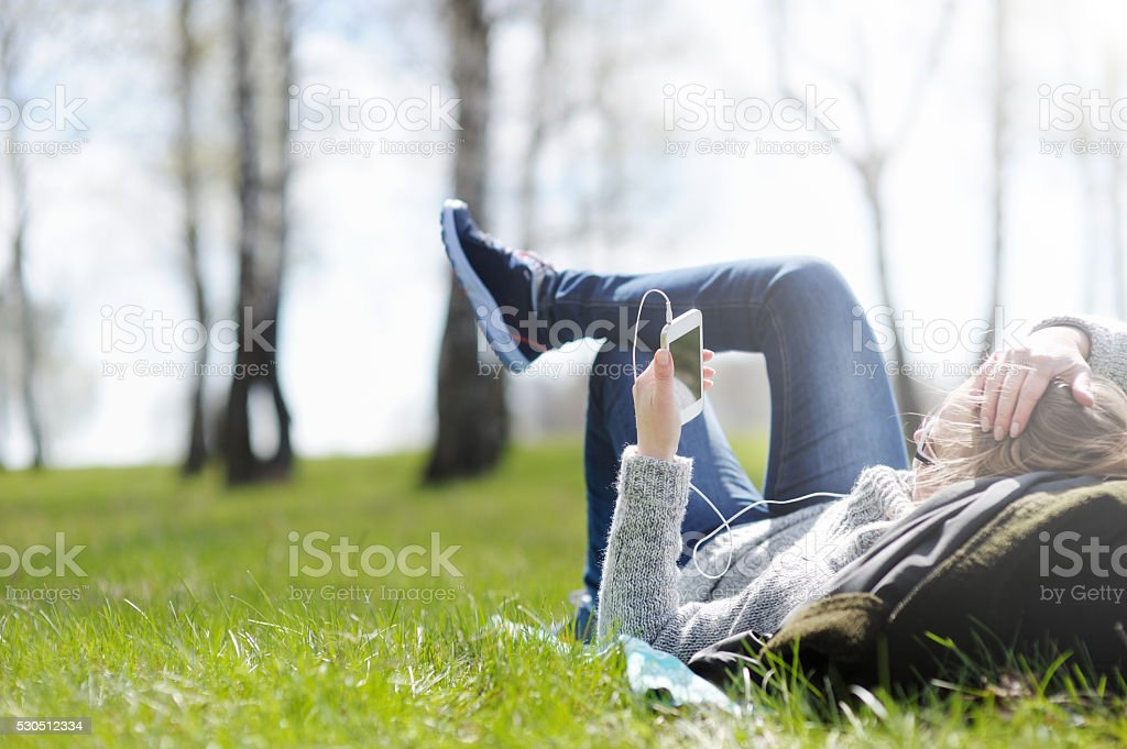 Young woman lying on grass in Park stock photo