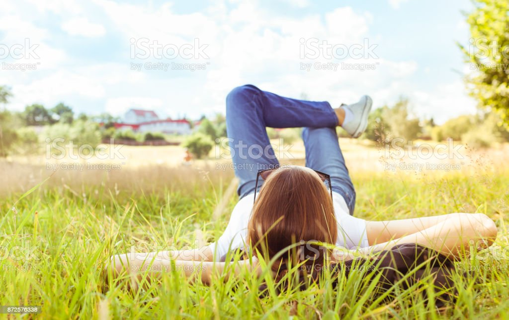 Young woman lying on grass looking up in the sky. stock photo