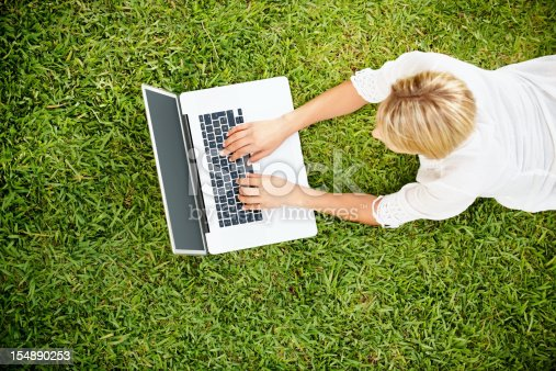 istock Young woman lying on green grass and using laptop 154890253
