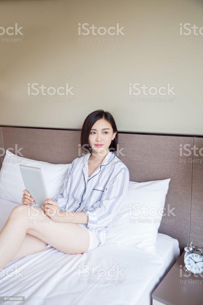 jeune femme allongée sur lit de maison à l'aide de tablette numérique photo libre de droits