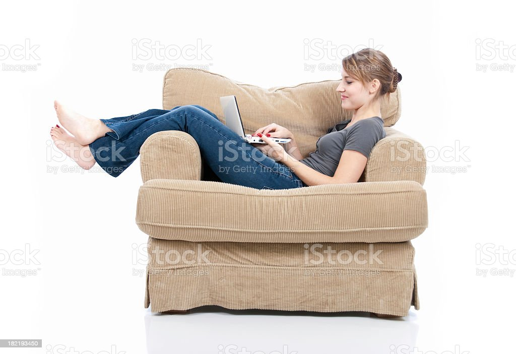 Young woman lying on lounge chair on laptop stock photo