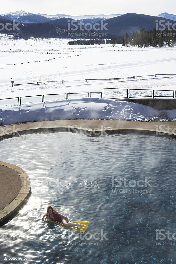 Young woman lying on pool raft, elevated view royalty free stockfoto