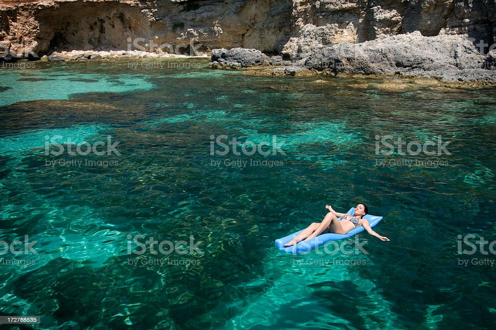 Young Woman Lying On Pool Raft, Mediterranean vacation stock photo
