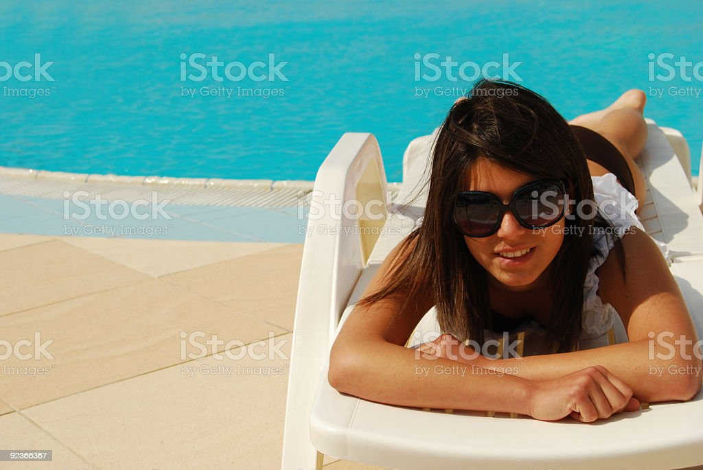 young woman lying on poolside royalty-free stock photo