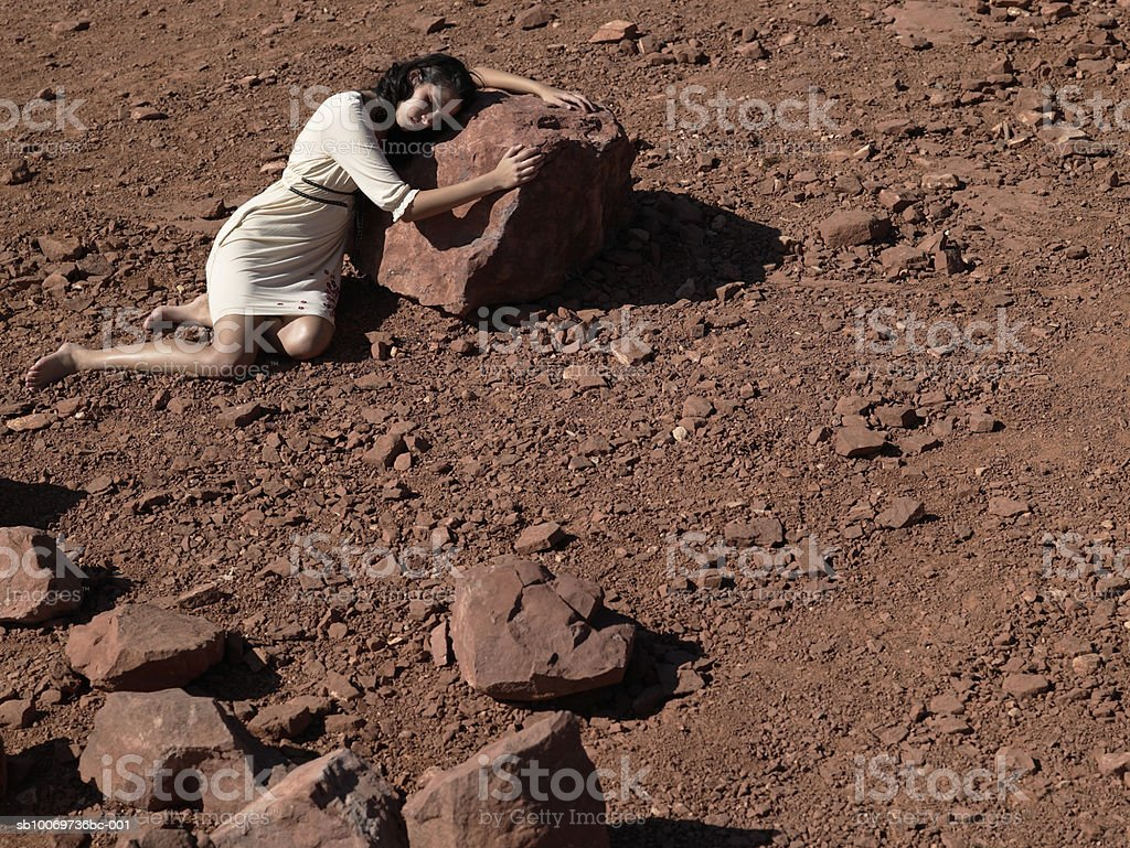 Young woman lying on rock, high angle view royalty-free stock photo