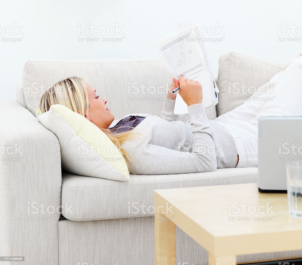 Young woman lying on sofa and writing documents royalty-free stock photo