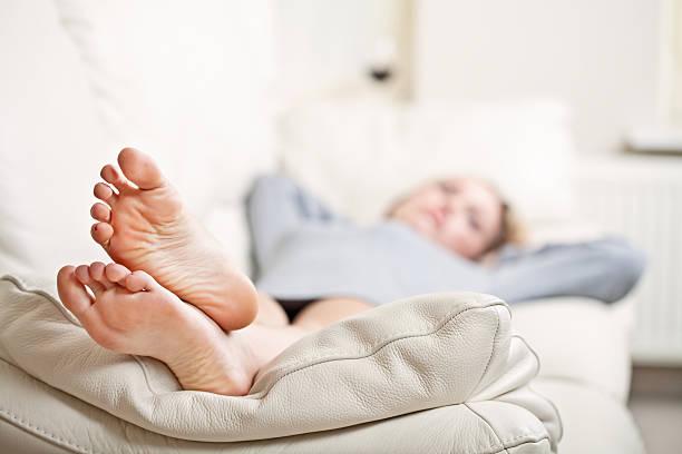 Young woman lying on sofa stock photo