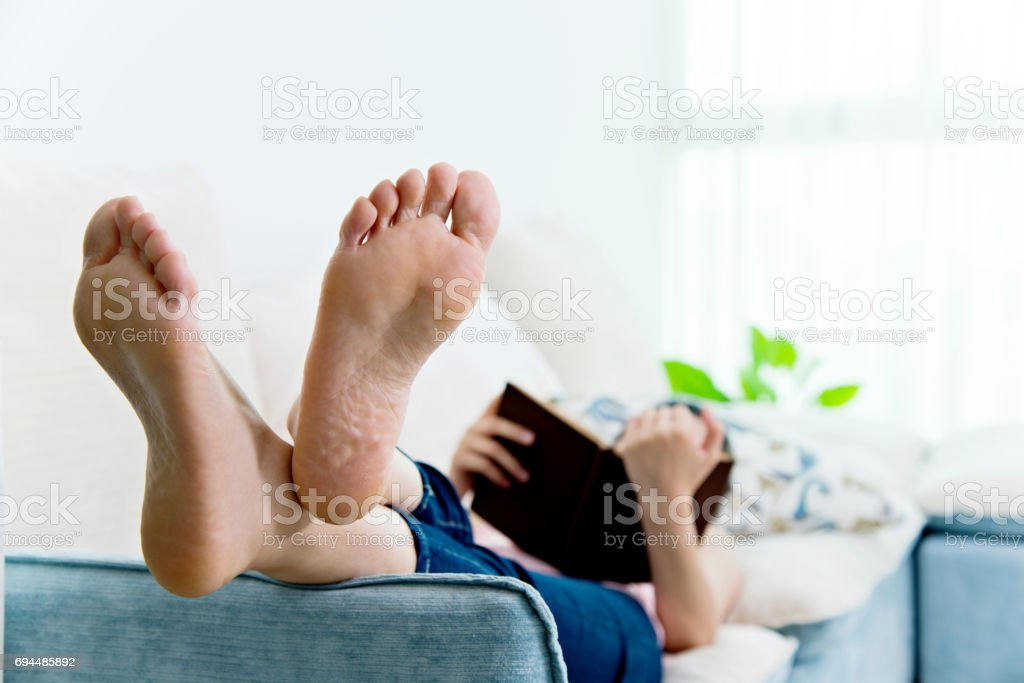 Young woman lying on sofa with book stock photo