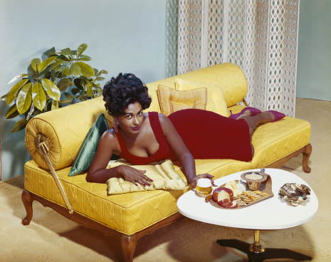 Young woman lying on sofa with snacks on table, portrait