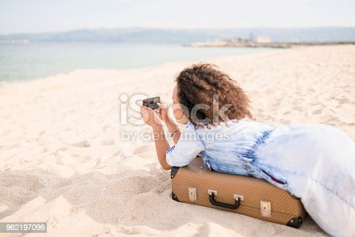 Young woman lying on suitcase and photographing. Exploring the South beach of Varna, Bulgaria on a summer day.