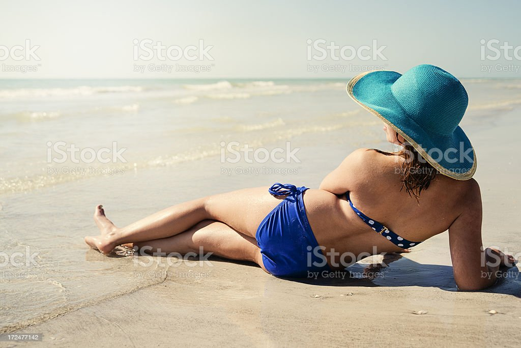 Young woman lying on the beach at sunset. royalty-free stock photo