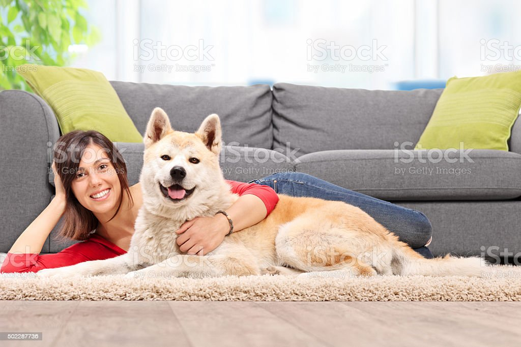 Young woman lying on the floor with her dog stock photo