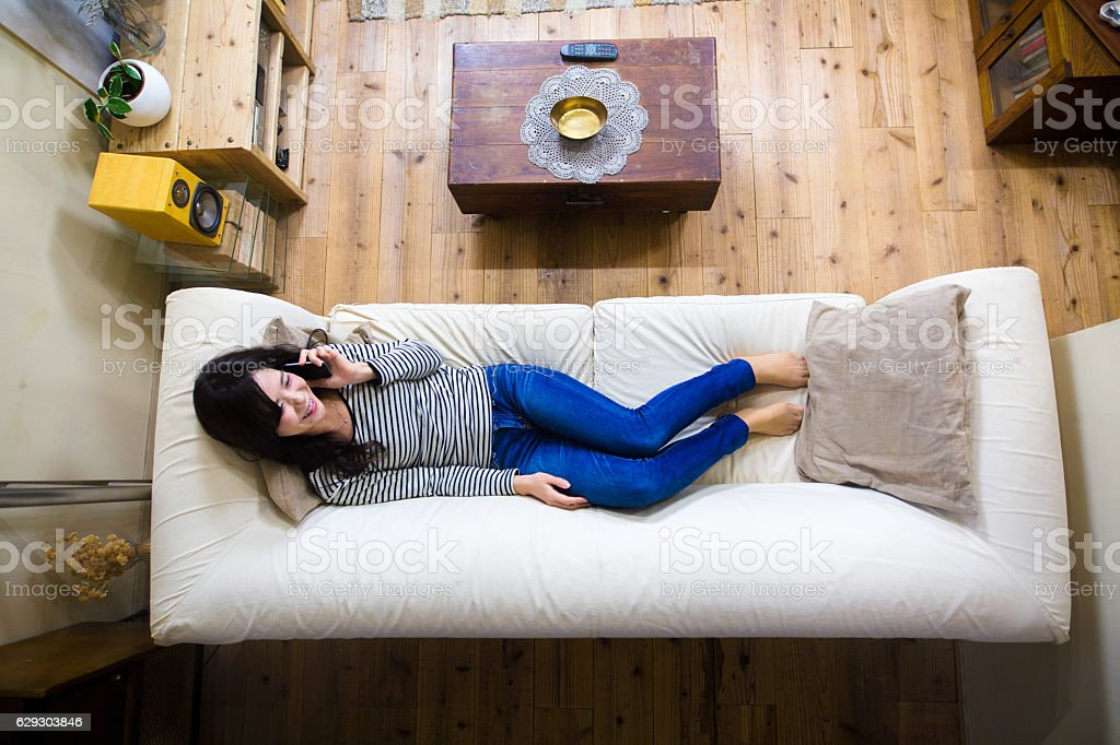 Young woman lying on the sofa talking on the phone stock photo