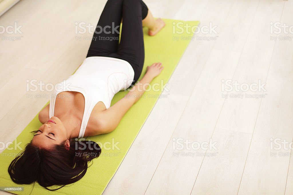 Young woman lying on the yoga mat royalty-free stock photo