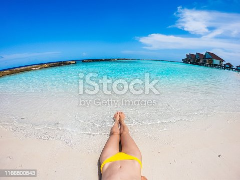 910785546 istock photo Young woman lying on tropical beach 1166800843