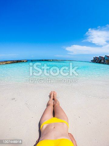 910785546 istock photo Young woman lying on tropical beach 1207446918
