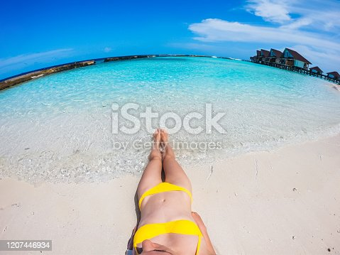 910785546 istock photo Young woman lying on tropical beach 1207446934