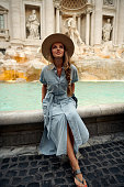 Italian vacations series. Young woman makes a wish at the Trevi Fountain