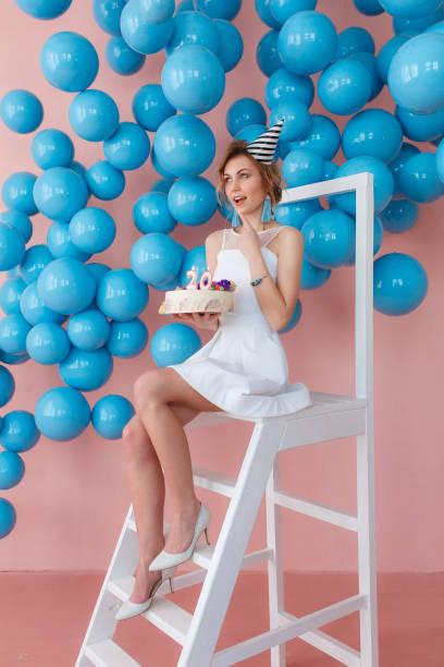 eine junge frau macht einen wunsch mit kuchen sitzen auf trittleiter auf rosa wand hintergrund mit blauen bläschen. 20er jahre kerzen - modetorten stock-fotos und bilder