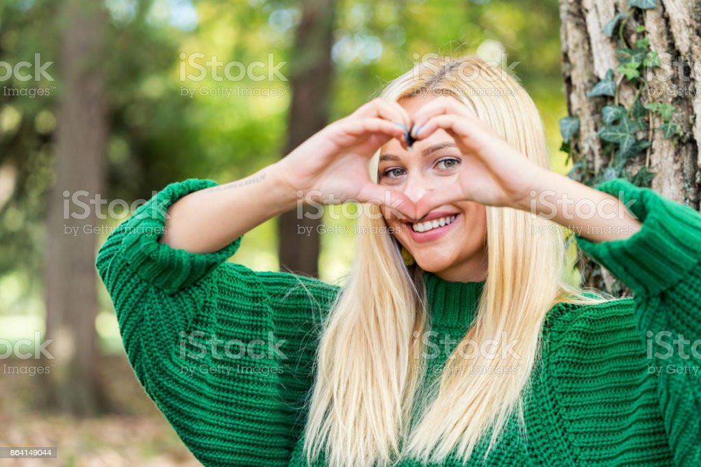 Young woman makes heart shape finger frame royalty-free stock photo