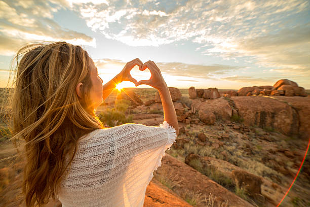 Young woman makes heart shape finger frame to spectacular landscape-sunrise stock photo
