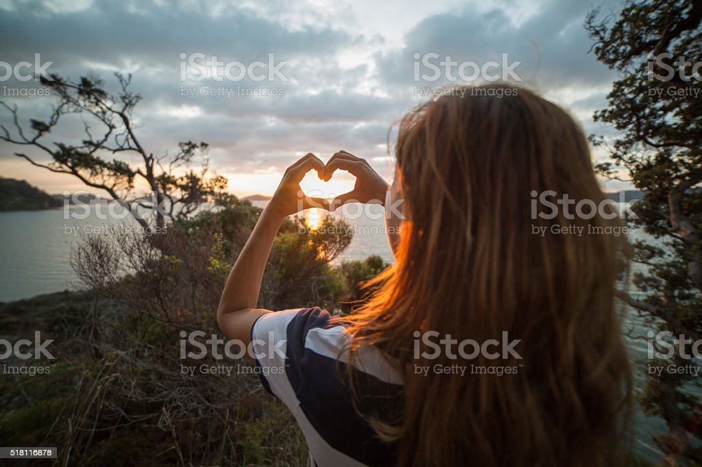 Young woman makes heart shape finger frame to sunset stock photo